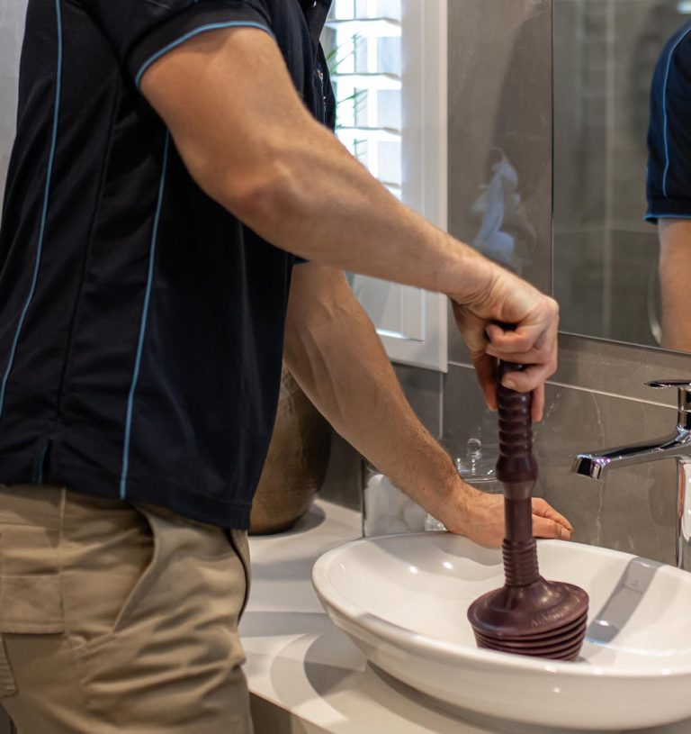 Plumber unblocks basin drain with plunger