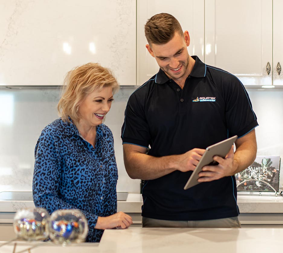 Aquatek plumber shows customer products on I pad in kitchen