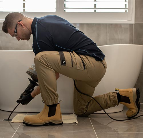 Plumber cleans bathroom drain with snake drain machine