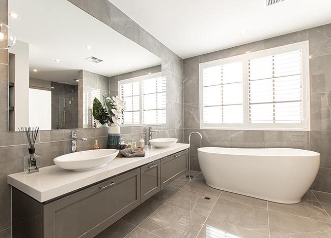 Bathroom with double vanity on stone bench top and free standing bath