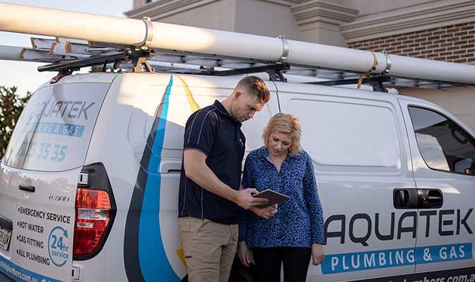 Aquatek emergency plumber in front of plumbing van with female customer