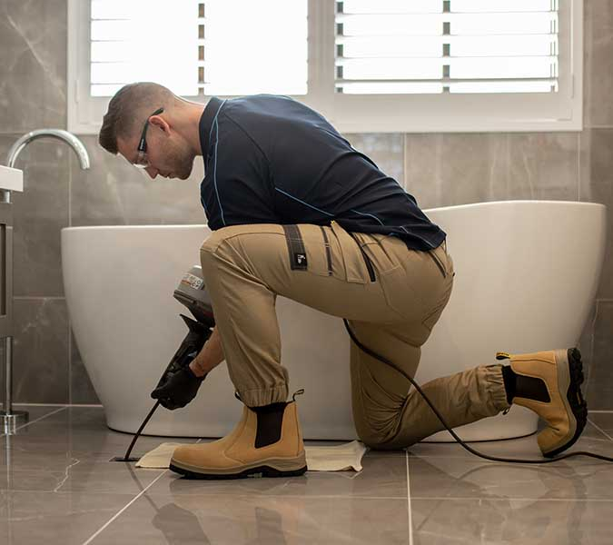 Plumber knees with drain machine over in-floor bathroom drain to clean the drain