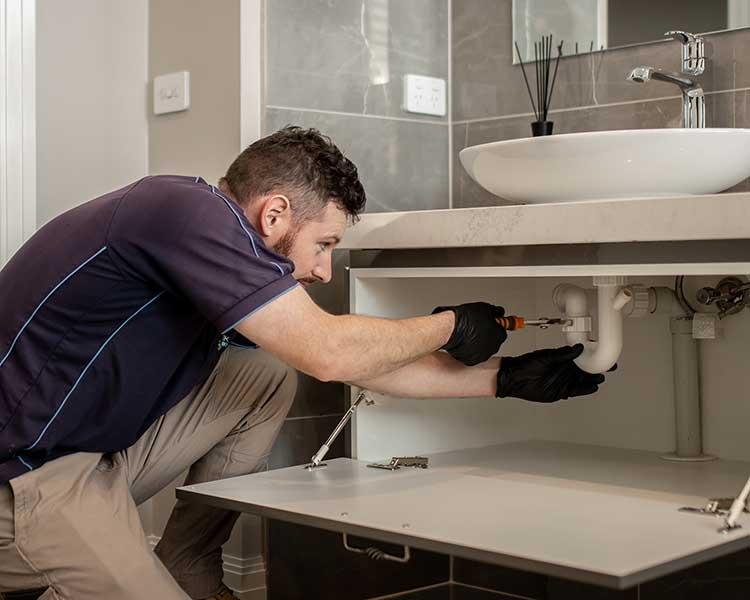 Plumber repairs pipes in a vanity underneath the bathroom basin