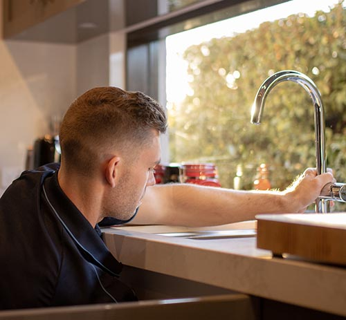 Plumber repairs kitchen mixer tap