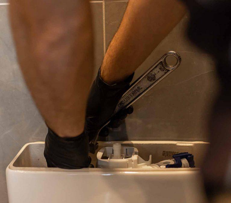 Plumber repairs toilet cistern