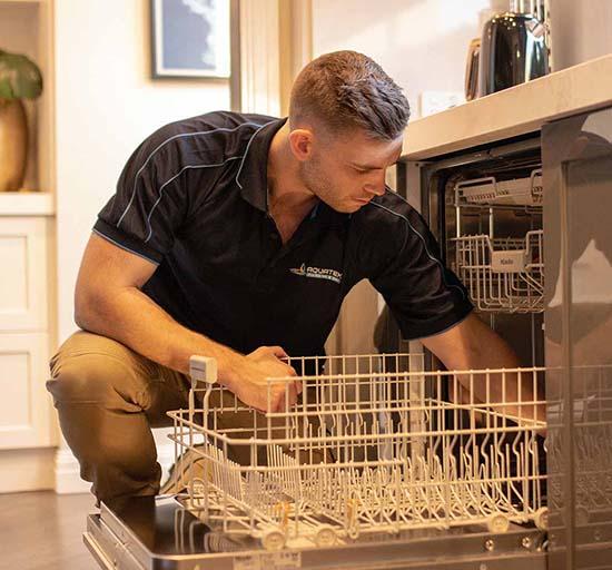 Plumber repairs dishwasher in kitchen