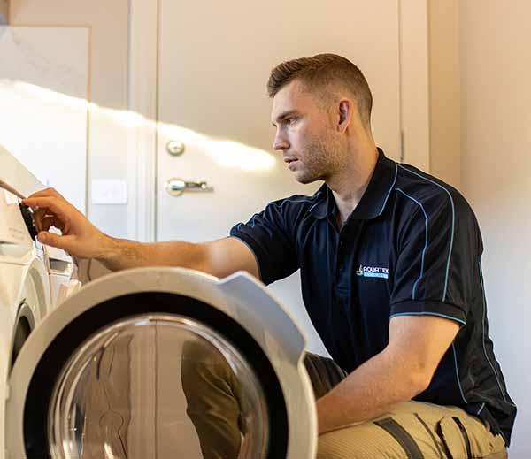 Plumber installs washing machine